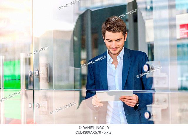 View through glass of man looking down at digital tablet smiling