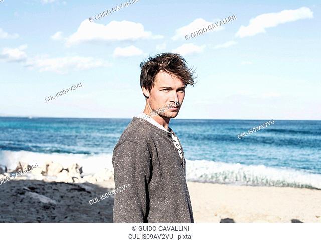 Young man on beach in front of ocean looking at camera, Costa Smeralda, Sardinia, Italy