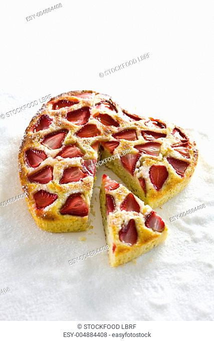 A heart-shaped cake with strawberries and lemongrass