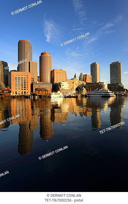City waterfront reflected in harbor