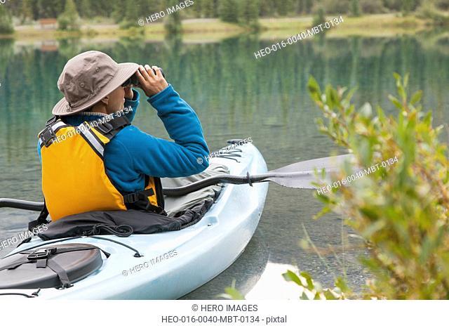 woman looking through binoculars while sitting in a kayak