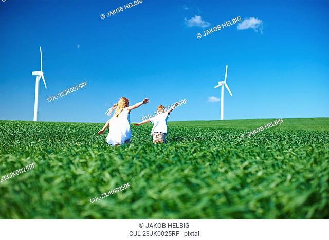 Childrens play in field & wind turbines
