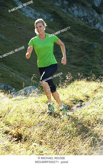 Austria, Kleinwalsertal, Young woman running on mountain trail