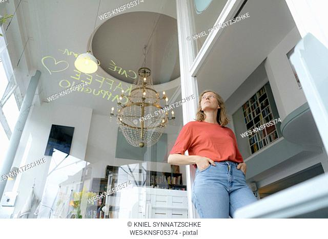 Low angle view of young woman standing in a cafe