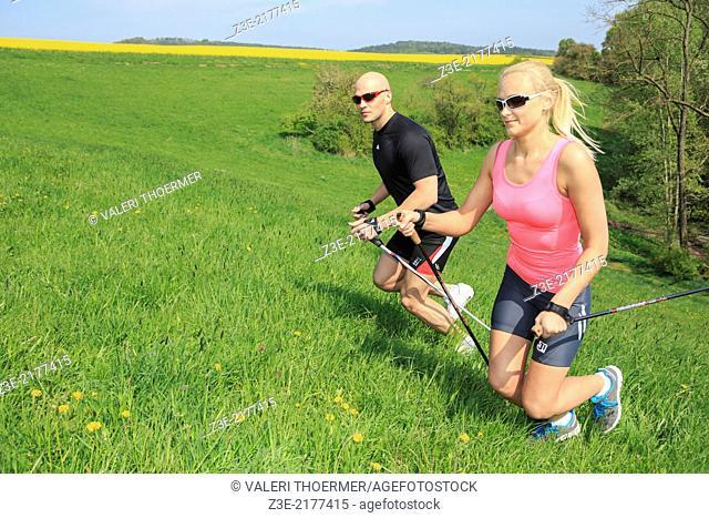 a couple making nordic walking training through rural landscape