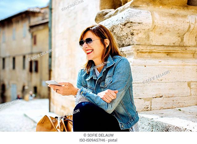 Mature woman holding smartphone, Tuscany, Italy