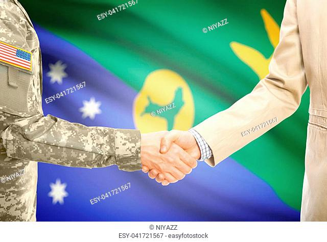 American soldier in uniform and civil man in suit shaking hands with adequate national flag on background - Christmas Island