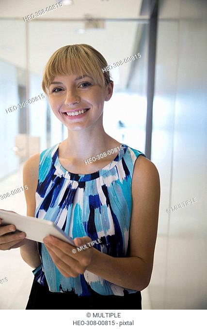 Portrait smiling businesswoman with digital tablet in office corridor
