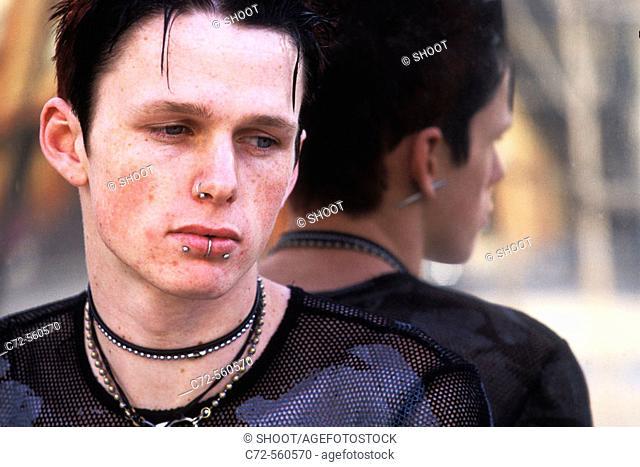 Rebellious teenage boy with facial piercings