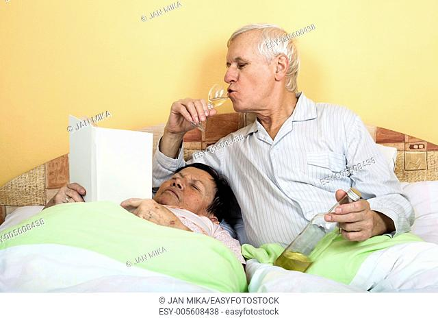 Funny senior couple relaxing in bed with alcohol and book