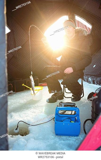 Ice fisherman sitting on chair with fish in his rod