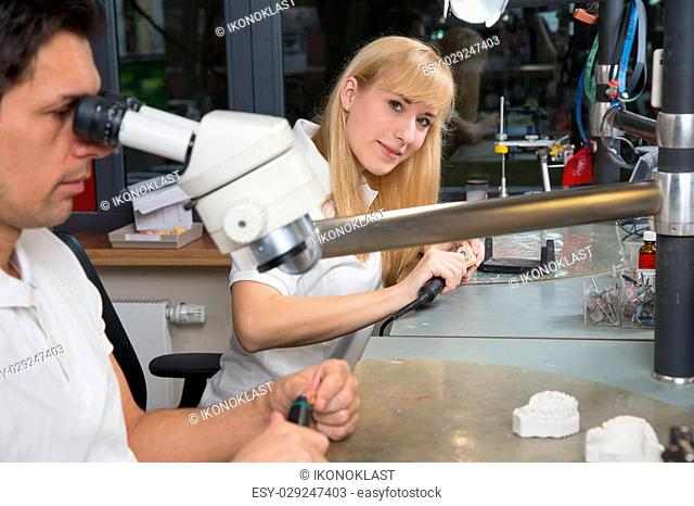 Dental technician smiling into the camera at work. She is producing a dental prosthesis