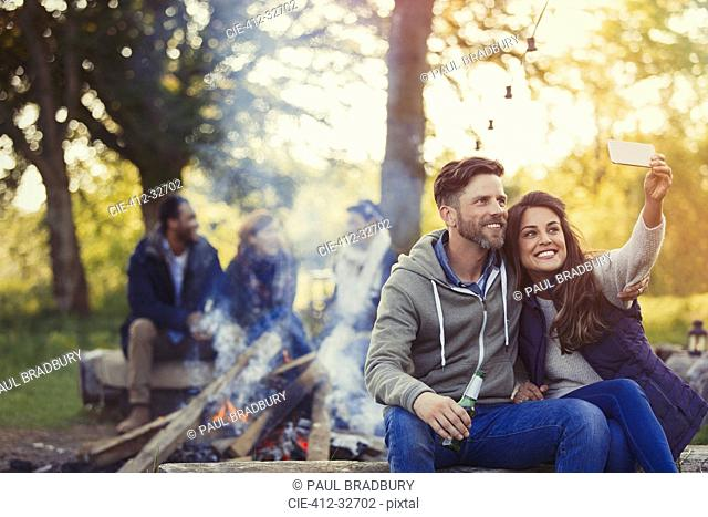Smiling couple taking selfie with camera phone near campfire