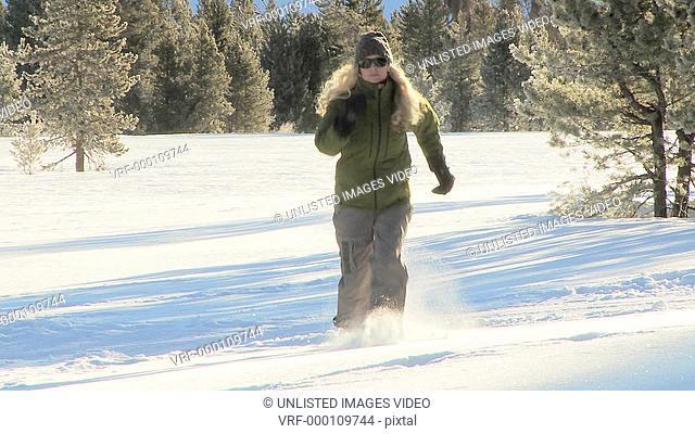 Woman wearing snow shoes runs through snow / Blaine County, Idaho, United States