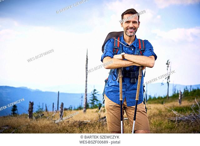 Portrait of smiling man having a break from hiking in the mountains