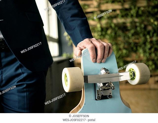Longboard in businessman's hand