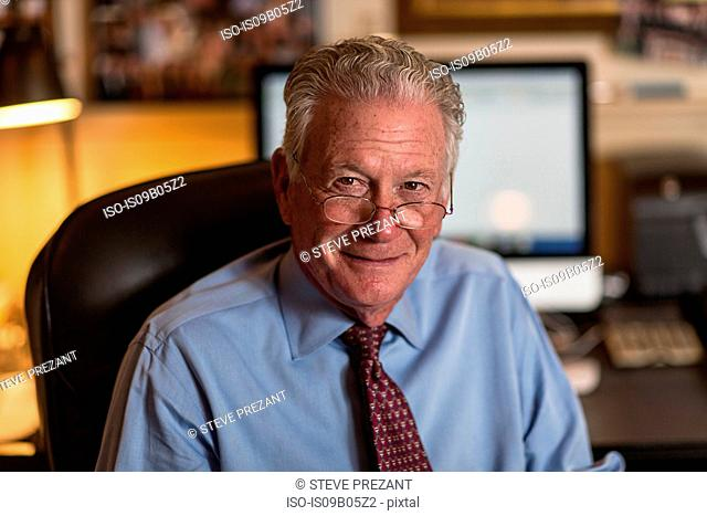 Portrait of senior businessman sitting on office chair