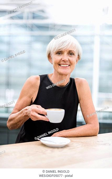 Portrait of smiling senior woman drinking a coffee