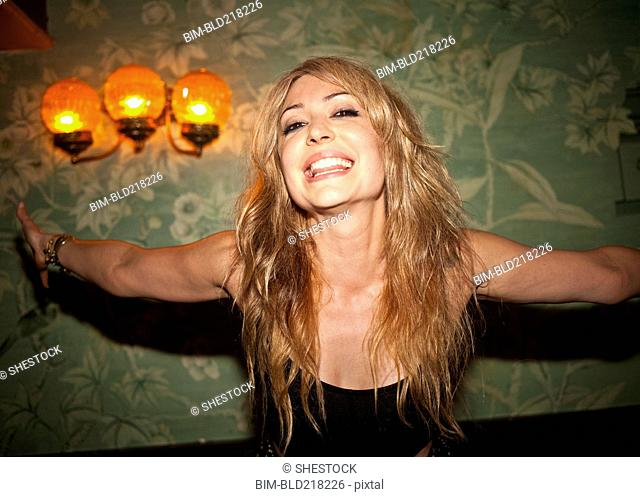 Smiling woman with arms outstretched