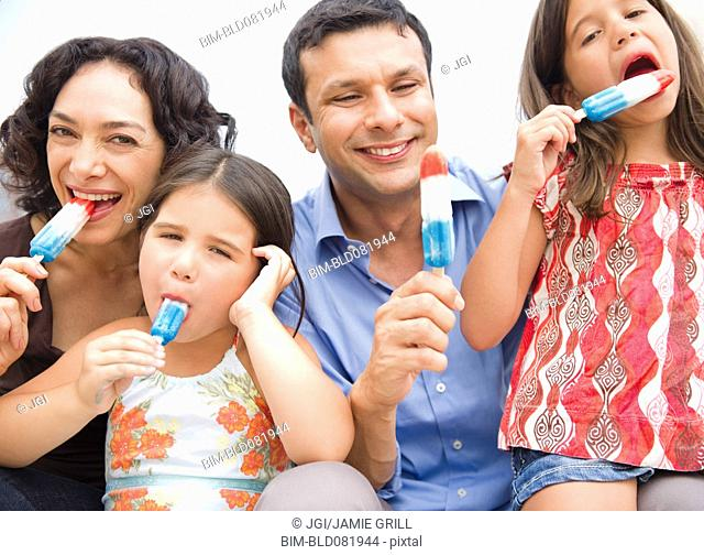 Smiling family eating popsicles together