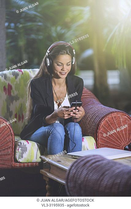Trendy brunette wearing headphones and surfing smartphone while sitting in armchair on hotel terrace