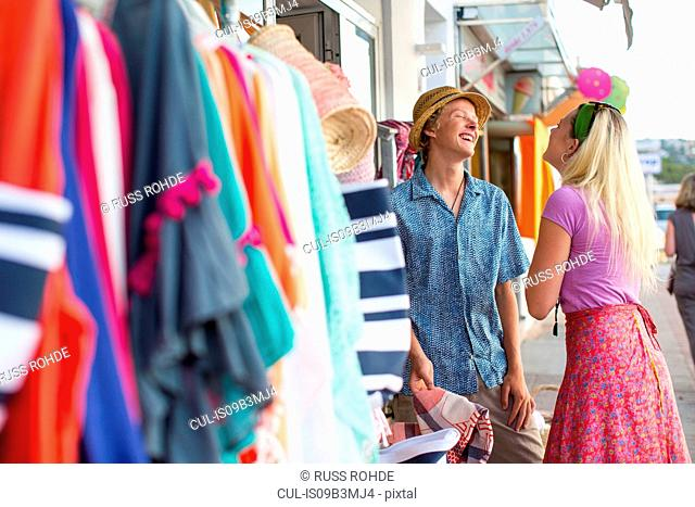 Young couple laughing trying sunhat at shop front, Majorca, Spain