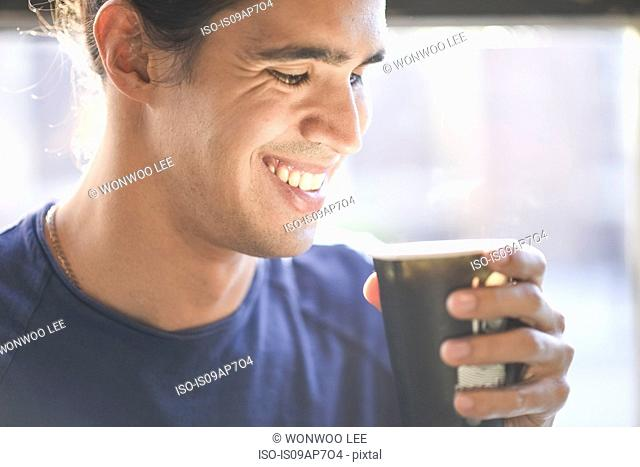 Young man holding coffee cup, indoors