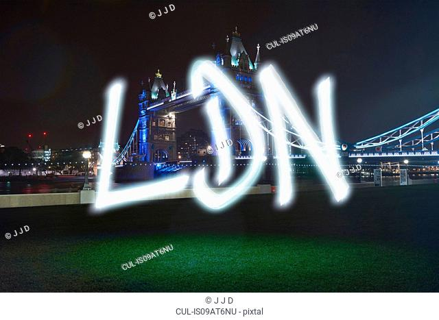 Glowing abbreviated London symbol in front of Tower Bridge at night