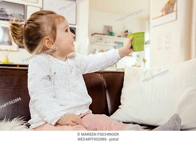 Little girl holding up a plastic cup while sitting on couch