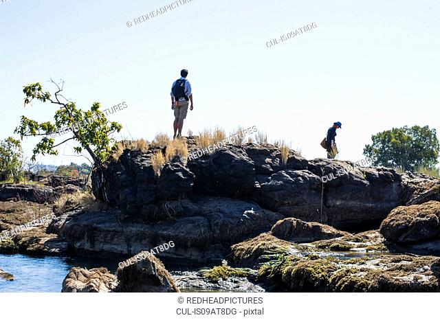 Couple exploring on rocks, near Victoria Falls, Zambia