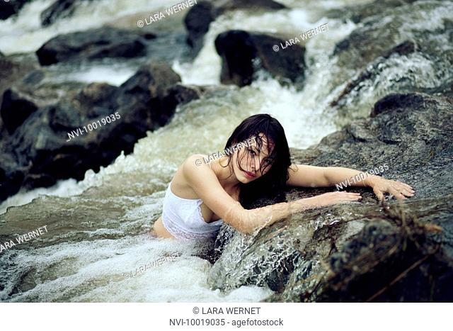 Young woman is sitting in a creek