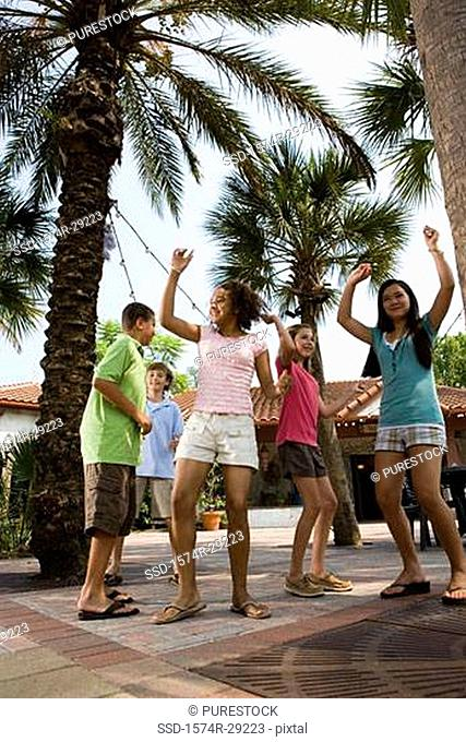 Teenagers dancing under a palm tree with a house in the background