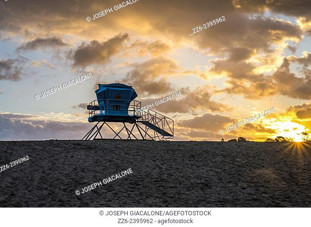 Sun rising on the horizon and a lifeguard tower on Ponto Beach. Carlsbad, California, United States