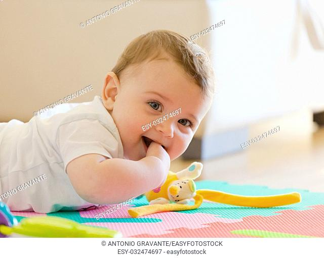 Toddler plays on the colored rubber mat