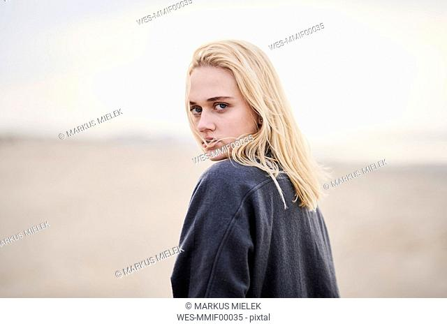 Portrait of serious blond woman on the beach