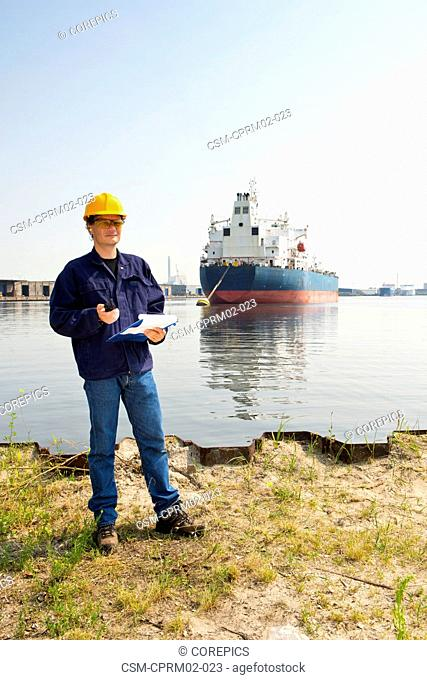 Docker posing on the water's edge with a clipboard and cb radio in his hand, in front of a large oil tanker, moored off in Amsterdam Harbor