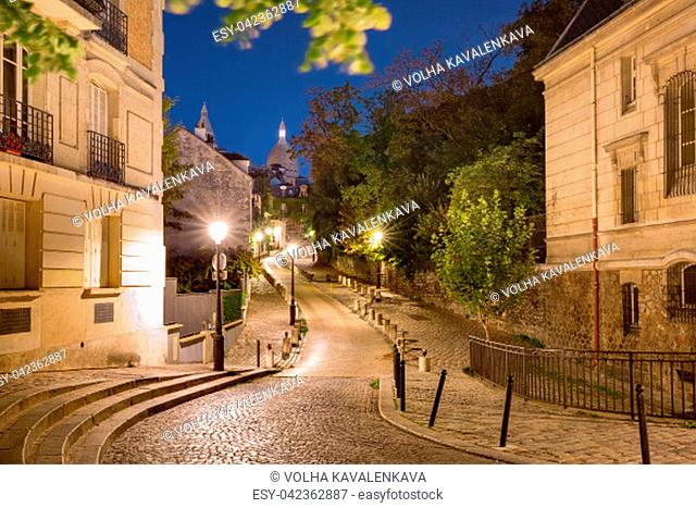 Empty cozy street and the Sacre-Coeur Basilica during morning blue hour, quarter Montmartre in Paris, France