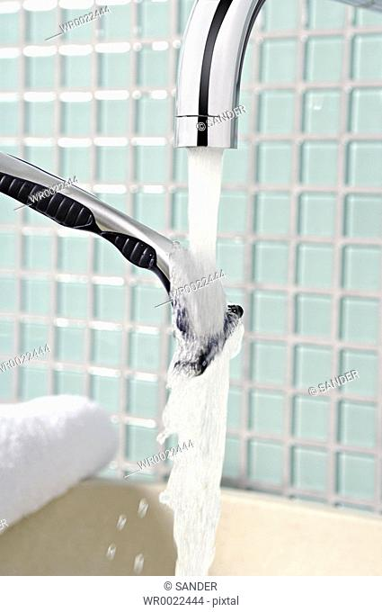 Razor being washed under faucet