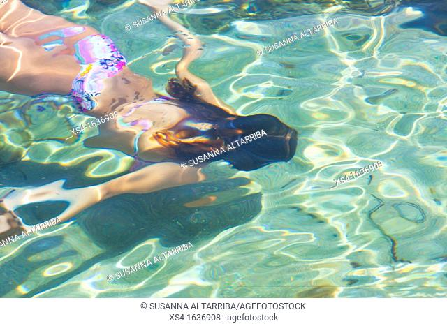 Young girl swim underwater in translucent water of Formentera, Balearic Island, Spain, Europe