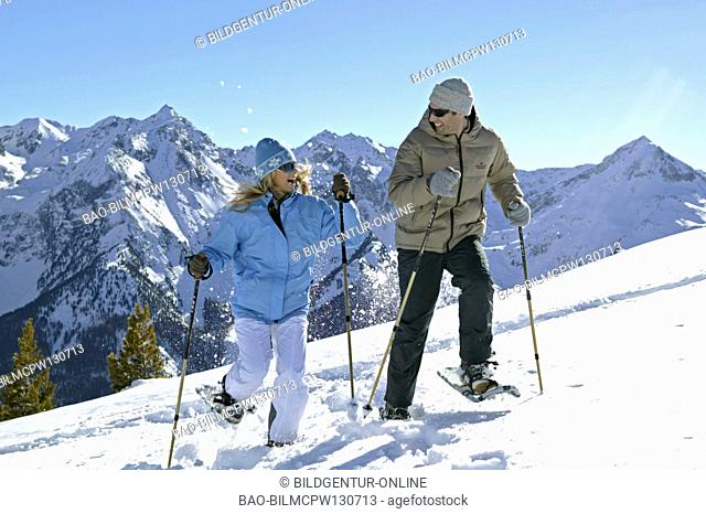 couple in winter hiking with snow shoes