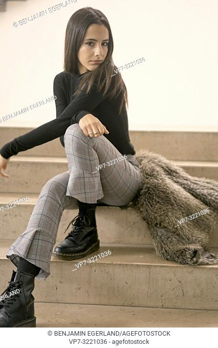 portrait of coy woman sitting on stairs, in Munich, Germany