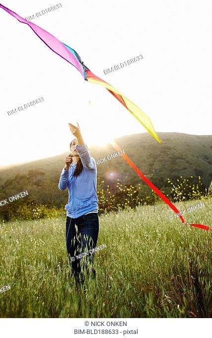 Asian woman flying kite in field