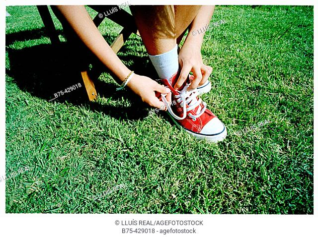 Girl lacing up shoes