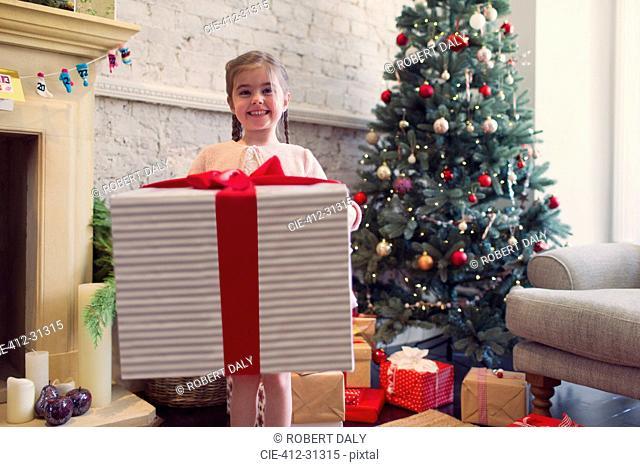 Portrait enthusiastic girl holding large Christmas gift