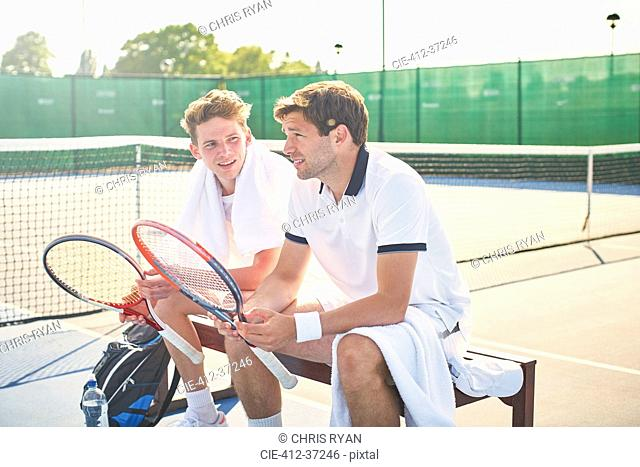 Young male tennis players resting with tennis rackets on sunny tennis court