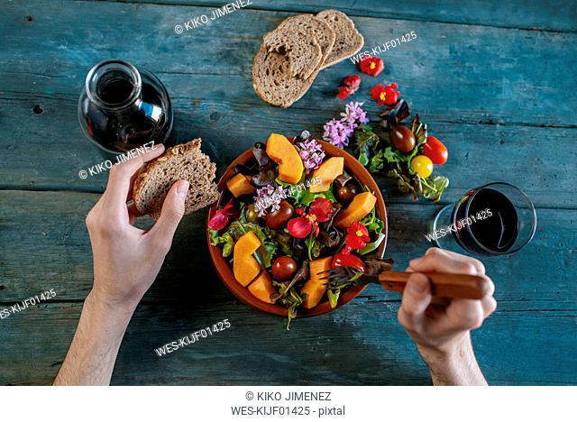 Close-up of man's hands eating mixed salad