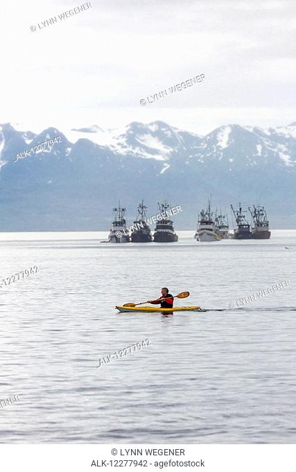 View of a kayaker in front of a group of seine fishing boats in Lynn Canal near Juneau, Southeast Alaska, Summer