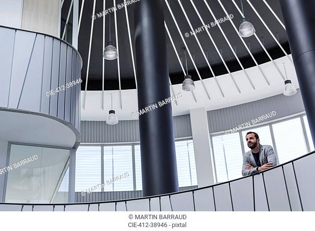 Pensive businessman on architectural, modern atrium balcony