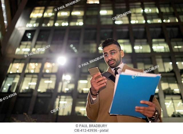 Businessman with paperwork and smart phone below urban highrise at night