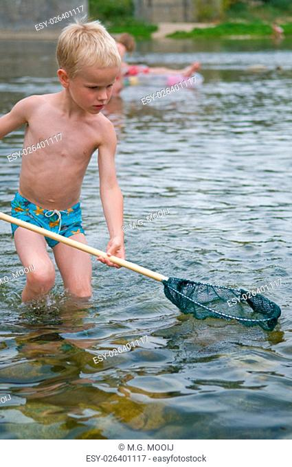 Young boy fishing with a fishing net in the Ardeche, France